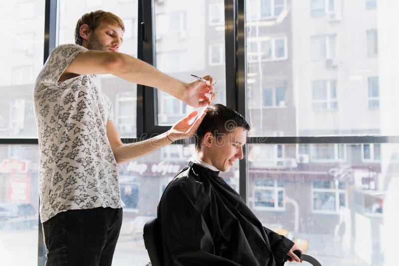 Mężczyzna ` s hairstyling i haircutting w fryzjera męskiego sklepie włosianym salonie lub zdjęcia stock