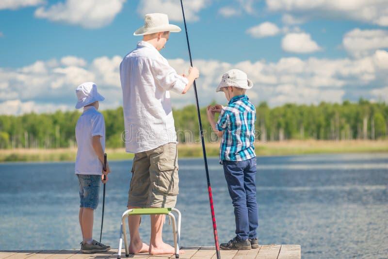 Mężczyzna ` s hobby - ojciec z jego synami na połowie w dobrym weathe obraz royalty free