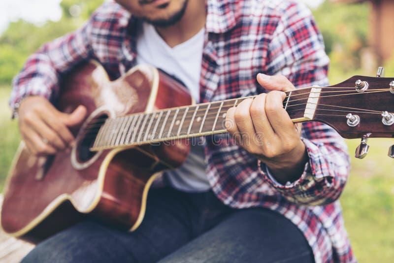 Mężczyzna ` s ręka bawić się gitarę, siedzi na zielonej trawie zdjęcia stock