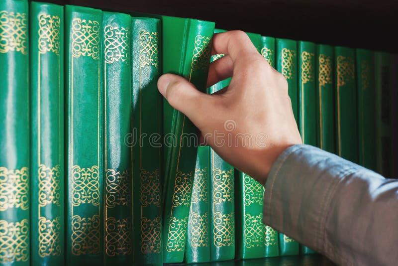 Mężczyzna ` s ręka bierze książkę z półka na książki zdjęcie royalty free