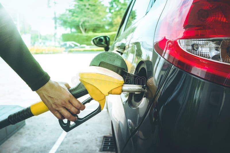 Mężczyzna ` s ręka pompuje benzyny paliwo w samochodzie przy benzynową stacją zdjęcie royalty free