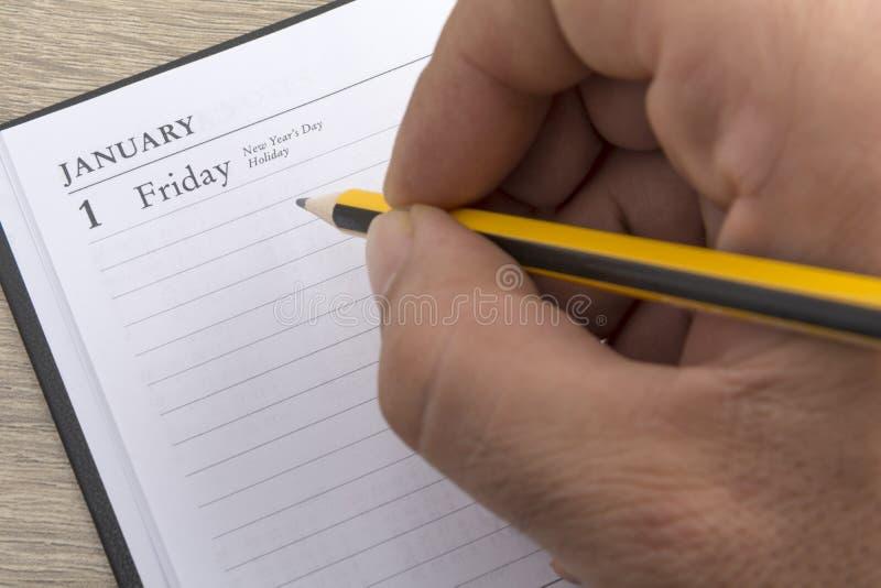 Mężczyzna ` s ręka trzyma ołówek przygotowywa ustawiać cele dla nowego roku zdjęcia royalty free