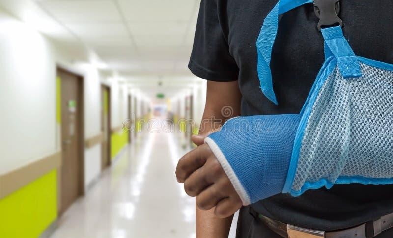Mężczyzna ` s ręka w obsadzie i temblak z zamazanym szpitalnym tłem zdjęcia stock