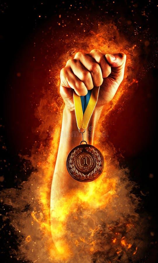 Mężczyzna ` s ręka w ogieniu trzyma up złotego medal Zwycięzca w rywalizaci obrazy royalty free