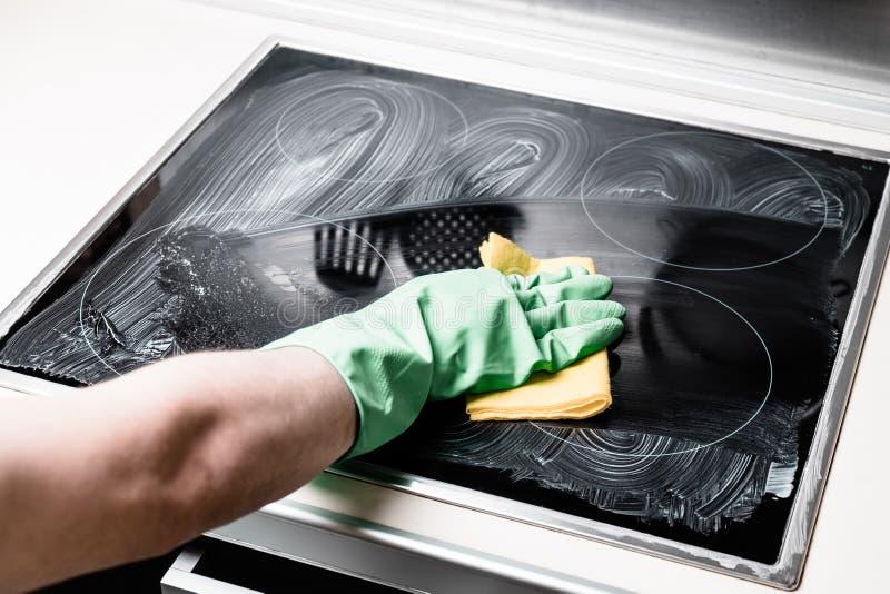Mężczyzna ` s ręka w zielonej rękawiczkowej cleaning kuchenki kuchni w domu fotografia stock