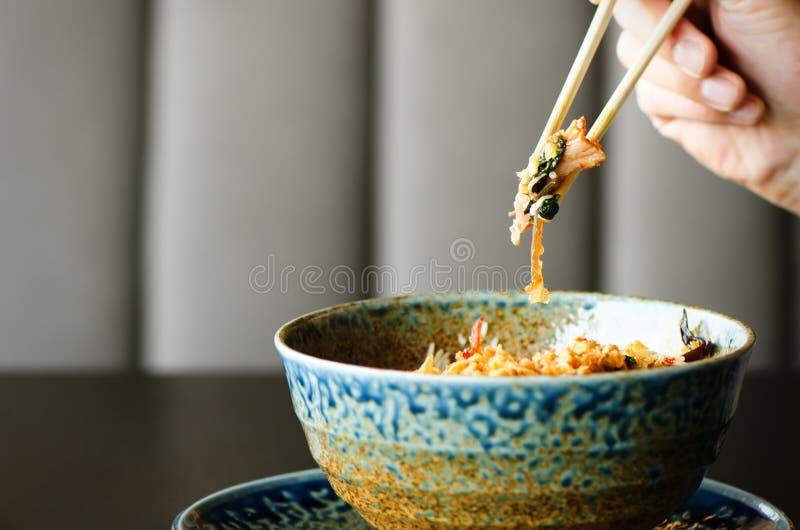 Mężczyzna ` s ręki mienia chopsticks nad talerzem japończyk, tajlandzki, chiński posiłek, - ryż, pieczarka, warzywa Kawiarnia obraz stock