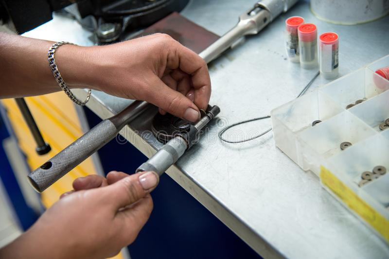 Mężczyzna ` s ręki mierzą leniwki specjalne uciskowe płuczki przystosowywać dieslowskich inżektory zdjęcia royalty free