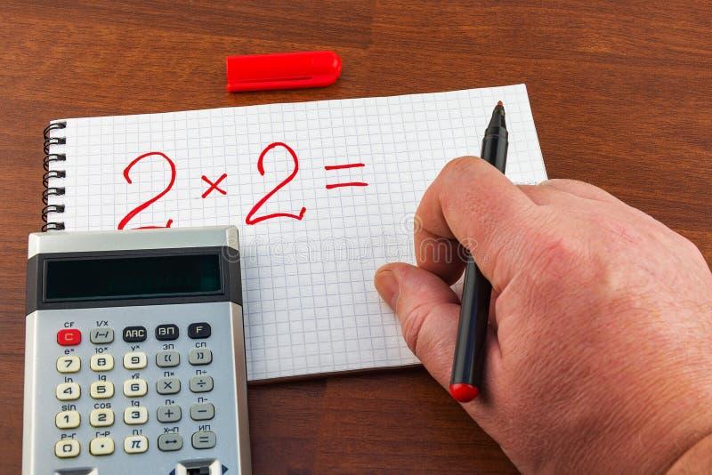 Mężczyzna ` s ręki writing równanie na notatnika prześcieradle w klatce zdjęcia royalty free