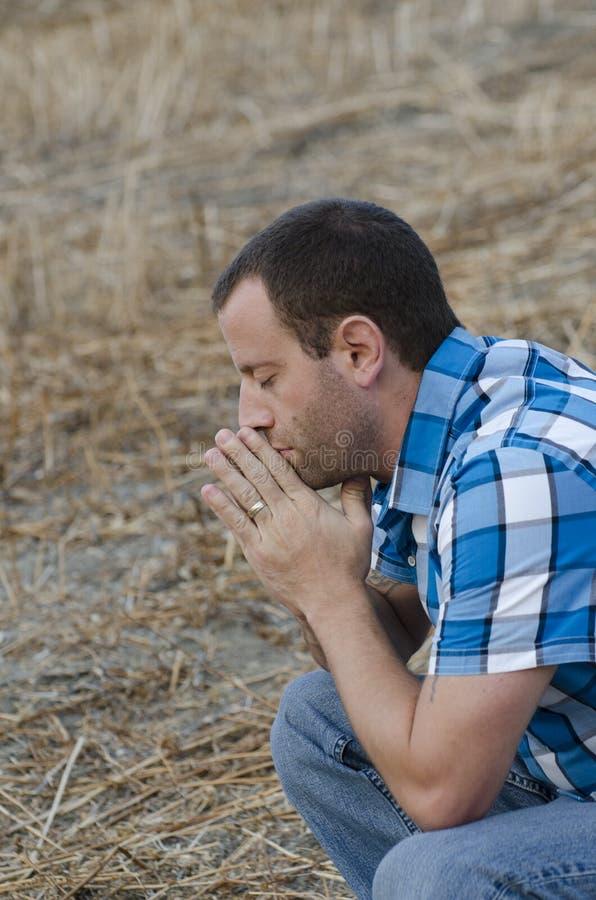 Mężczyzna samotnie w modlitwie w polu obrazy royalty free