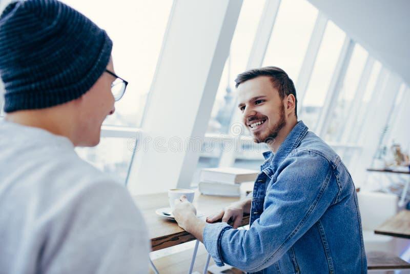 Mężczyzna siedzą przed stołowym pobliskim okno zdjęcia royalty free