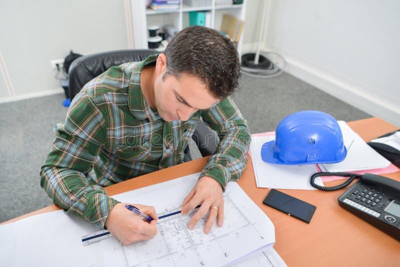 Mężczyzna siedzący przy biurkiem pracuje na projektach zdjęcia royalty free