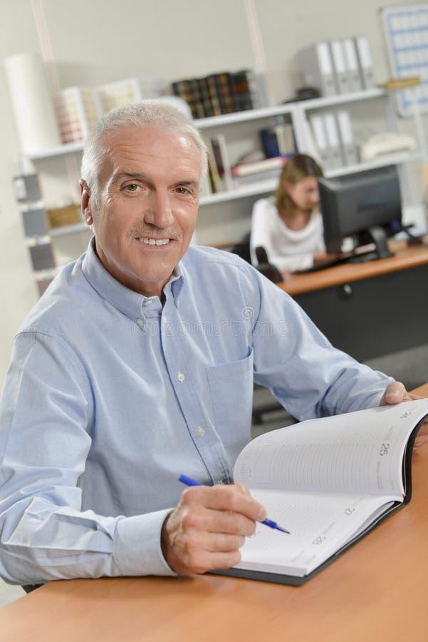 Mężczyzna siedzący przy biurkiem z otwartym dzienniczkiem zdjęcia stock