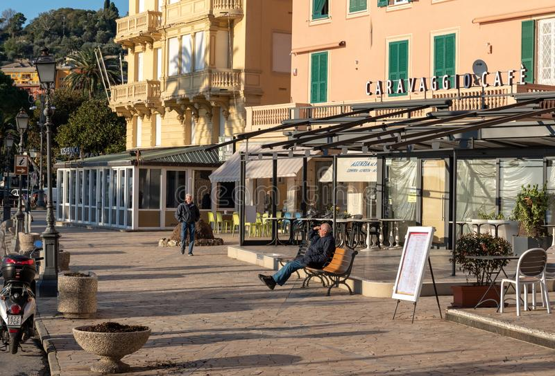 Mężczyzna siedzi na ławce przy środkową ulicą miasteczko fotografia stock