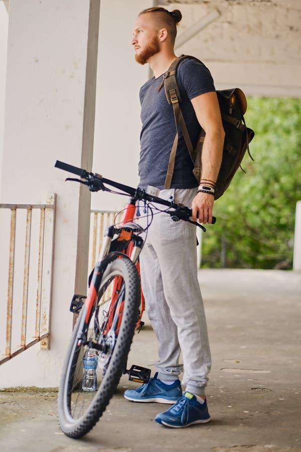 Mężczyzna siedzi na czerwony halny rowerowy plenerowym obrazy stock