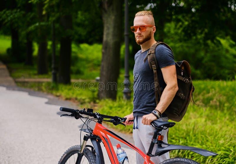 Mężczyzna siedzi na czerwony halny rowerowy plenerowym zdjęcia stock