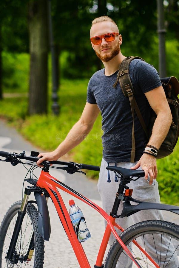 Mężczyzna siedzi na czerwony halny rowerowy plenerowym zdjęcie stock