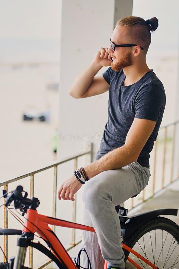 Mężczyzna siedzi na czerwonym halnym bicyklu i trzyma smartphone obrazy royalty free