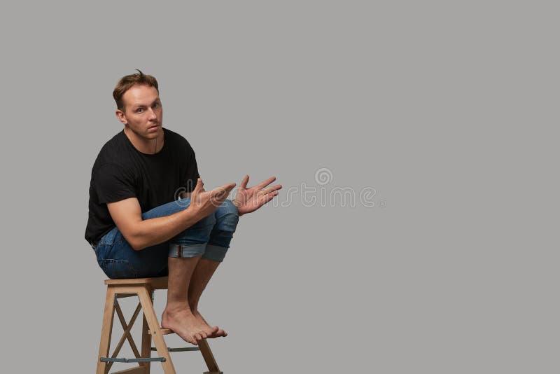Mężczyzna siedzi na krześle w czarnej koszulce i cajgach pokazuje z jego rękami na twój tekscie lub twój reklamie na szarości obrazy royalty free