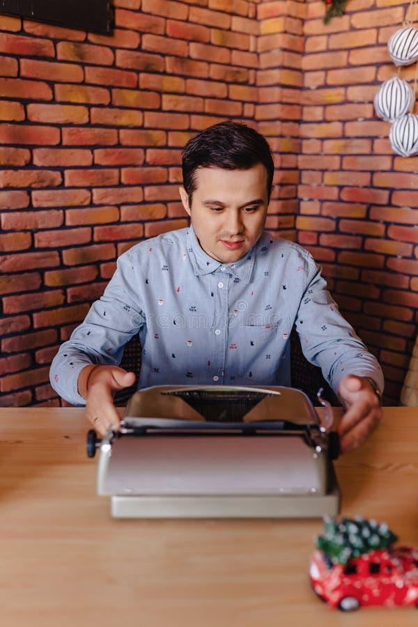 Mężczyzna siedzi na maszynie do pisania w świątecznym nastroju z szkłem obraz stock
