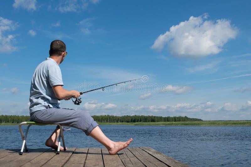 mężczyzna siedzi na molu na krześle i chwyty łowią na przędzalnictwie, plenerowy odtwarzanie fotografia stock