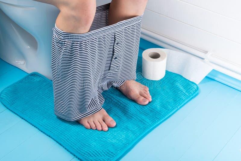 Mężczyzna siedzi na pchnięciu w toalecie z jego majtkami usuwającymi, on zaparcie, widok z góry fotografia royalty free