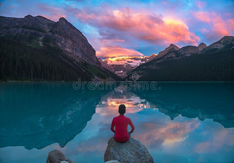 Mężczyzna siedzi na rockowym dopatrywaniu Jeziorne Louise ranku chmury z odbijają fotografia royalty free