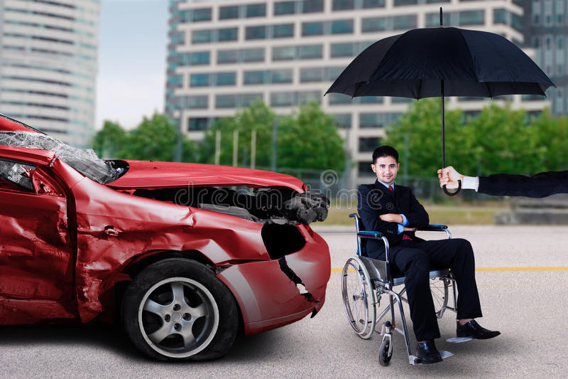Mężczyzna siedzi na wózku inwalidzkim z uszkadzającym samochodem zdjęcie stock