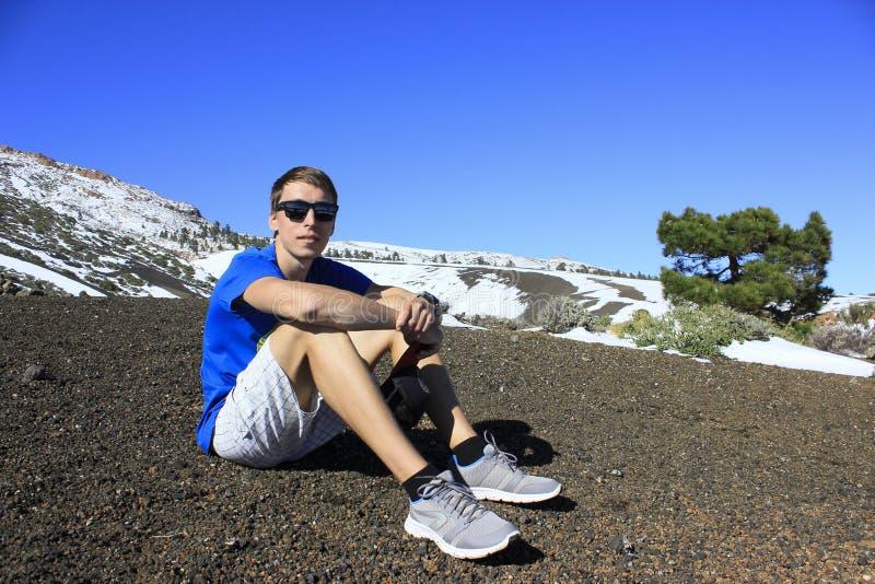 Mężczyzna siedzi na ziemi przy stopą śnieżna góra zdjęcie stock