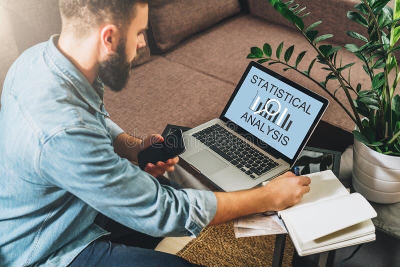 Mężczyzna siedzi przy stołem i robi notatkom w jego notatniku, działanie, uses laptop z wpisową statystyczną analizą na ekranie zdjęcie stock