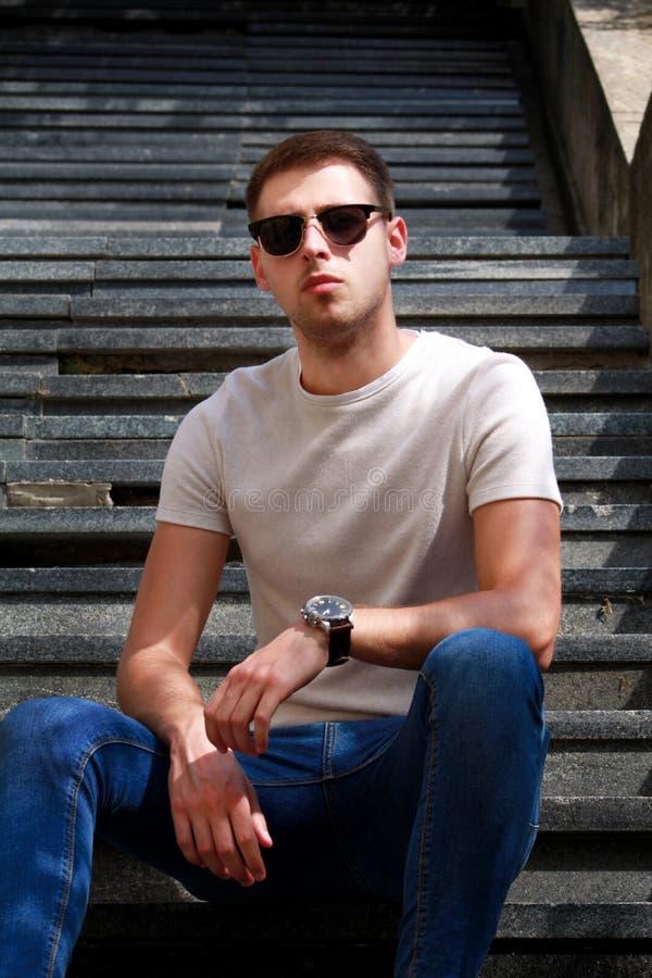 Mężczyzna siedzi samotnie na krokach Przystojna chłopiec z okularami przeciwsłonecznymi Samiec wzorcowy pozować dla strzelać, sie fotografia stock