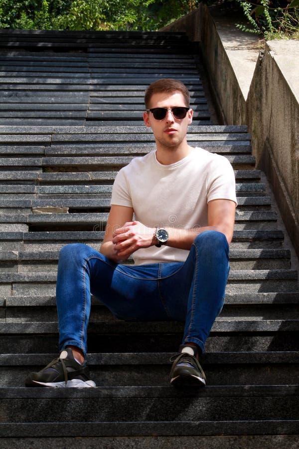 Mężczyzna siedzi samotnie na krokach Przystojna chłopiec z okularami przeciwsłonecznymi Samiec wzorcowy pozować dla strzelać, sie obrazy stock
