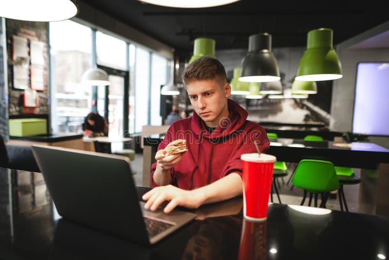 Mężczyzna siedzi w fast food restauracji, trzyma hamburger w jego rękach, używa internet na laptopie, skupia się na ekranie obraz stock