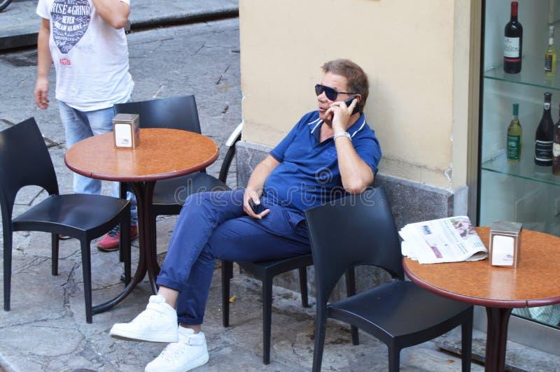 Mężczyzna siedzi w plenerowym cukiernianym cieszy się czasie wolnym opowiada na telefonie komórkowym w okularach przeciwsłoneczny obraz royalty free