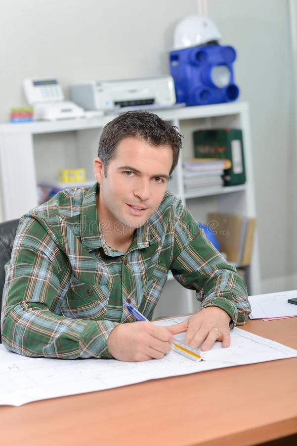 Mężczyzna siedział przy biurkiem pracuje na szalkowych rysunkach obrazy royalty free