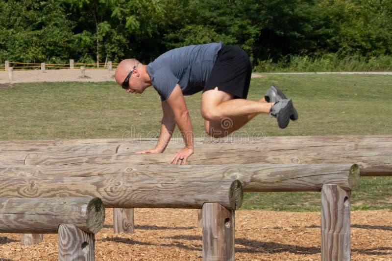 Mężczyzna skacze loguje się przeszkoda kurs zdjęcie royalty free