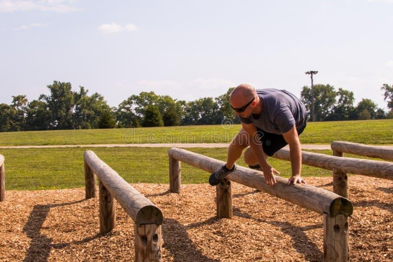 Mężczyzna skacze loguje się przeszkoda kurs fotografia royalty free