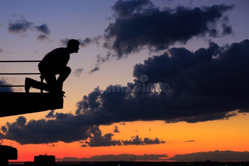 Mężczyzna skacze od krawędzi dach cloud słońca fotografia stock