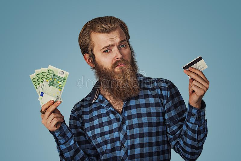 Mężczyzna skeptical wybiera plastikowa karta kredytowa lub pieniędzy banknotów gotówkowi euro rachunki zdjęcie royalty free