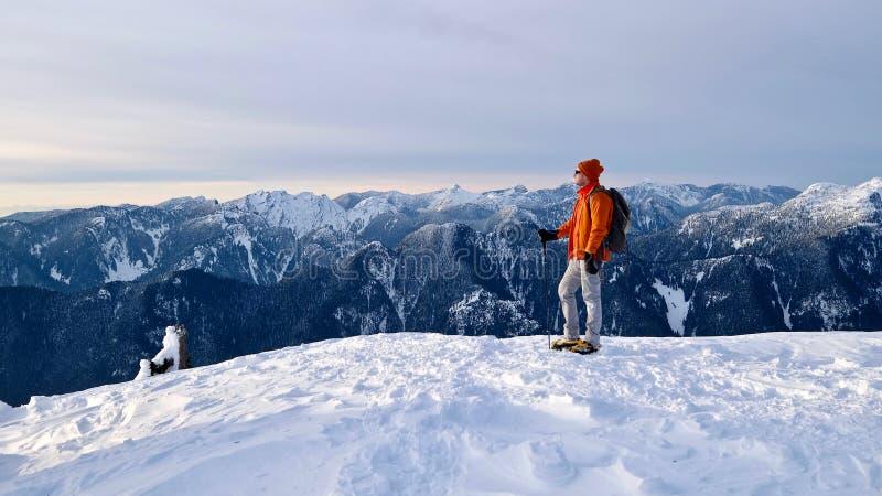 Mężczyzna snowshoeing na góra wierzchołku fotografia stock