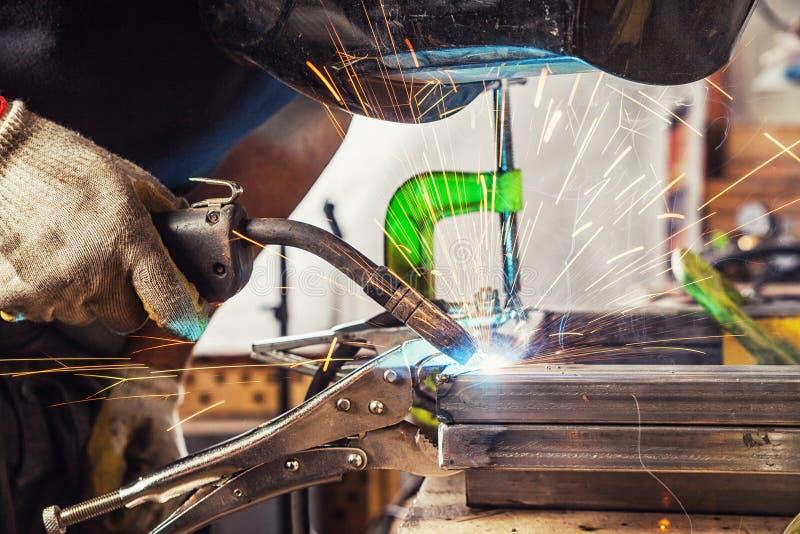 Mężczyzna spawa metal spawalniczą maszynę obrazy royalty free