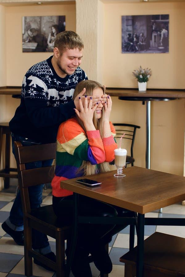 Mężczyzna spotyka kobiety w kawiarni facet znacząco no kraść w górę i zamykać jego oczy dziewczyna para jest uśmiechnięta zdjęcie stock