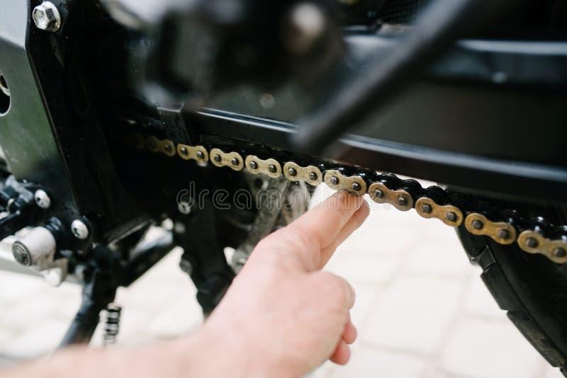 Mężczyzna sprawdza łańcuszkowego napięcie w motocyklu fotografia royalty free