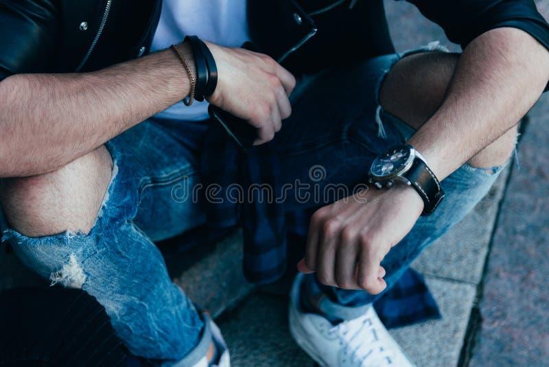 Mężczyzna sprawdza czas w obdartych cajgach i czarnej kurtce, ulica styl mężczyzna ` s ręka z zegarkiem i w innej ręce trzyma a obrazy royalty free