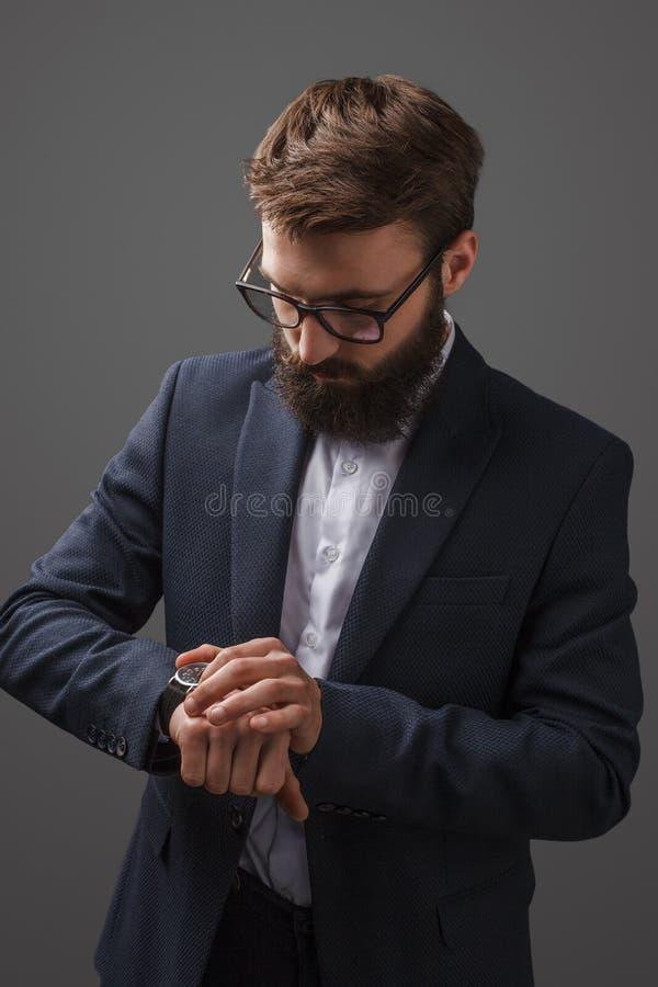 Mężczyzna sprawdza czas w studiu w kostiumu obrazy royalty free