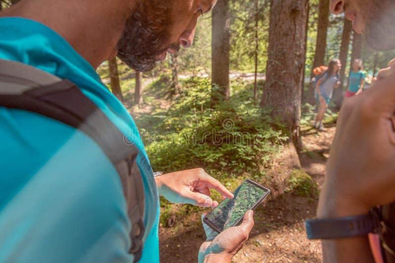 Mężczyzna sprawdza smartphone gps mapę przy wycieczkować ślad ścieżkę w lesie w fotografia royalty free