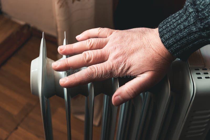 Mężczyzna sprawdza temperaturę elektryczny nafciany nagrzewacz z jego ręką W poza sezonem, środkowym ogrzewaniu, zawsze no pracuj obraz stock