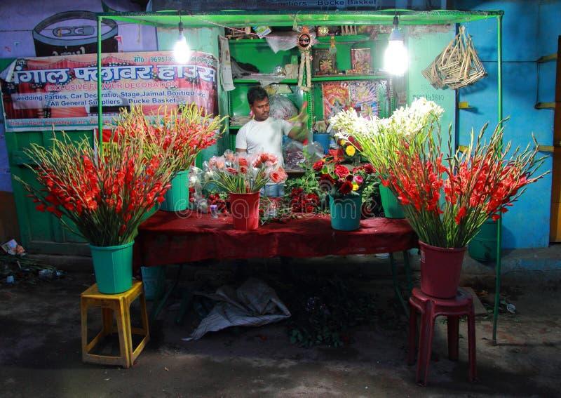 Mężczyzna sprzedaje kwiaty plenerowych w Varanasi, India obraz stock
