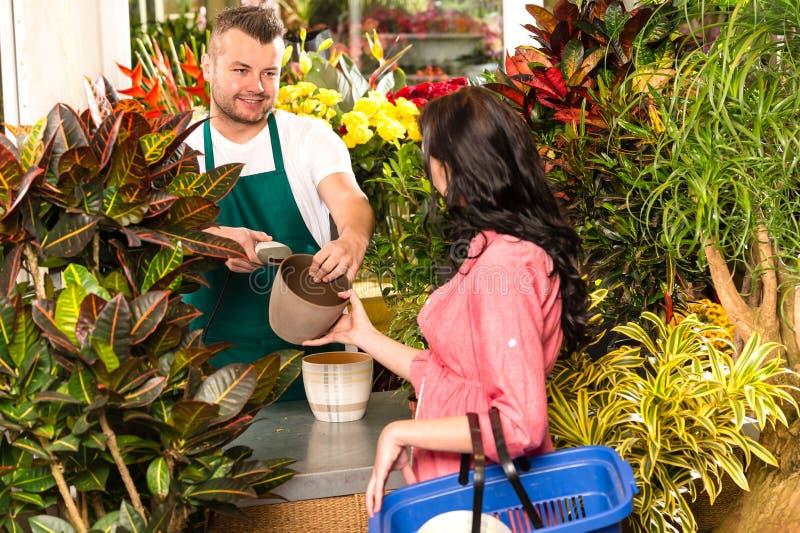 Mężczyzna sprzedawania garnka kobiety klienta kwiatu sklep zdjęcia stock