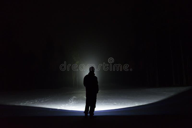Mężczyzna stać plenerowy przy nocą w lasowym jaśnieniu z latarką naprzód obrazy royalty free