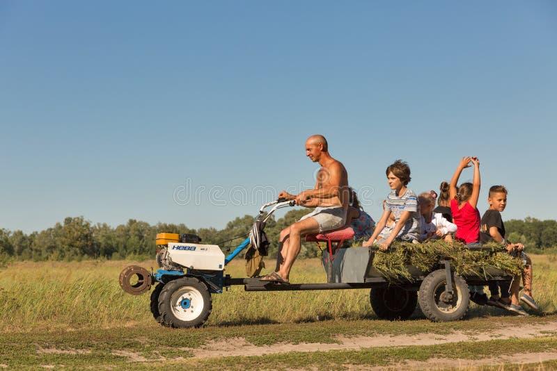 Mężczyzna stacza się dzieci na mini ciągniku w Koncha-Zaspa, Ukraina fotografia stock